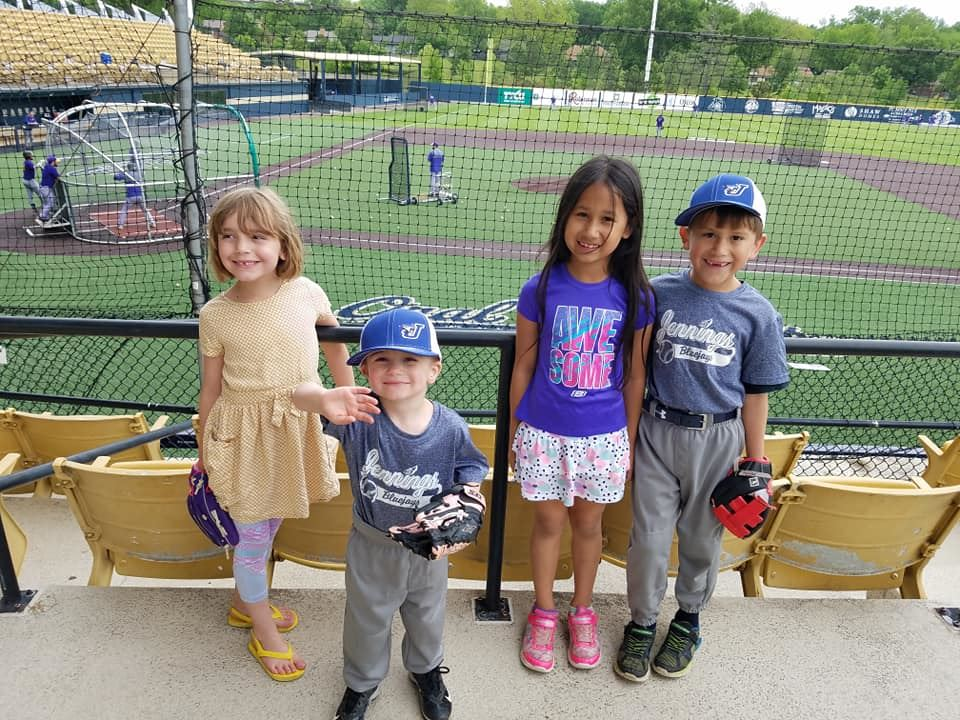 Picture of four children at a baseball game